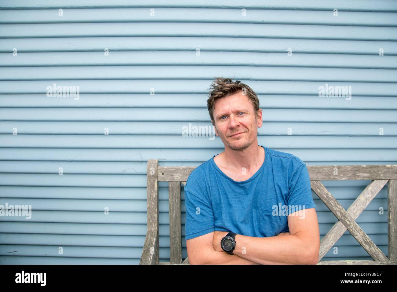 Stati Uniti, California, Pacific Grove, uomo seduto su una vecchia panca di legno Immagini Stock
