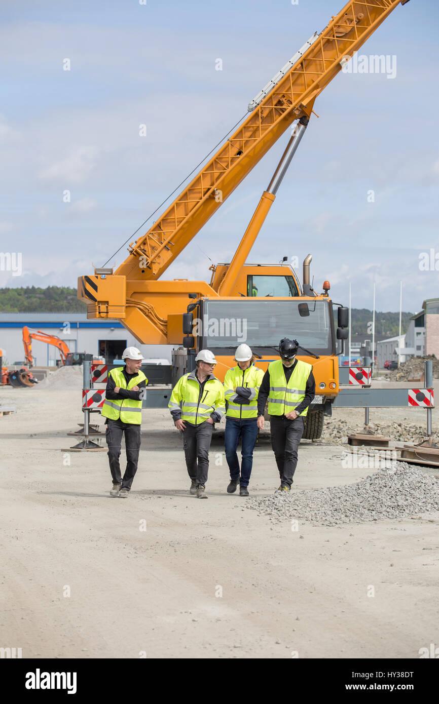 La Svezia, Halland, kungsbacka, lavoratori edili a piedi con gru in background Immagini Stock