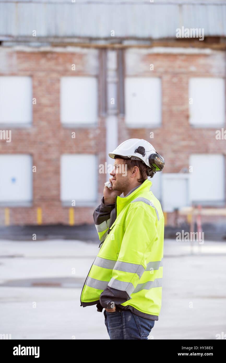 La Svezia, l'uomo utilizza lo smartphone nel sito in costruzione Immagini Stock