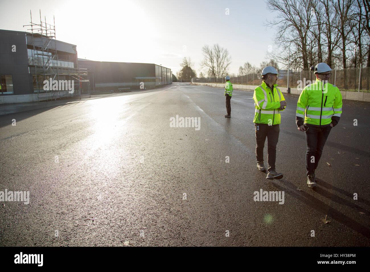 La Svezia, uomini maturi indossando indumenti da lavoro protettiva in strada al di fuori del sito in costruzione Immagini Stock