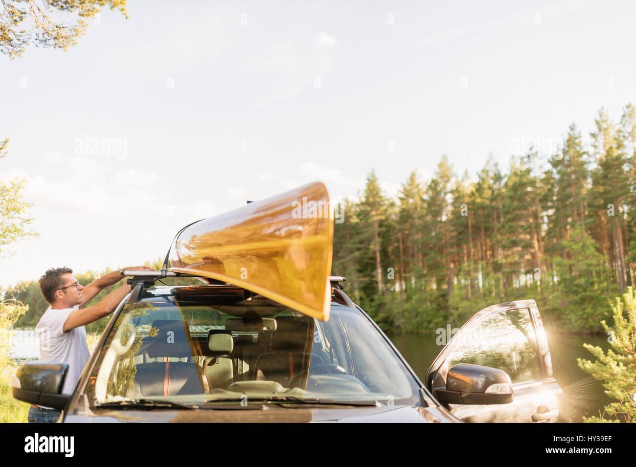 La Svezia, vastmanland, hallefors, bergslagen, man standing in auto con kayak sul tetto Immagini Stock