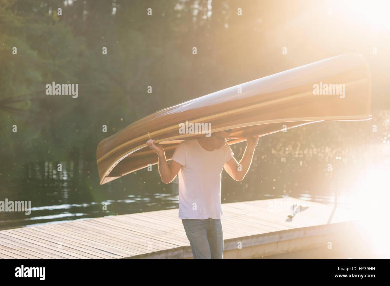 La Svezia, vastmanland, hallefors, bergslagen, uomo di legno portante canotto sulla testa Immagini Stock