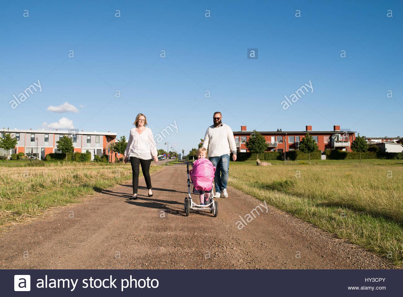La Svezia, genitori e figlia (2-3) passeggiate in ambiente rurale Immagini Stock