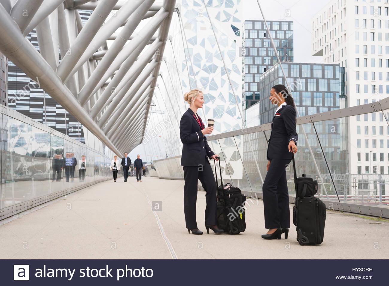 Norvegia, Oslo, hostess in piedi con le valigie Immagini Stock