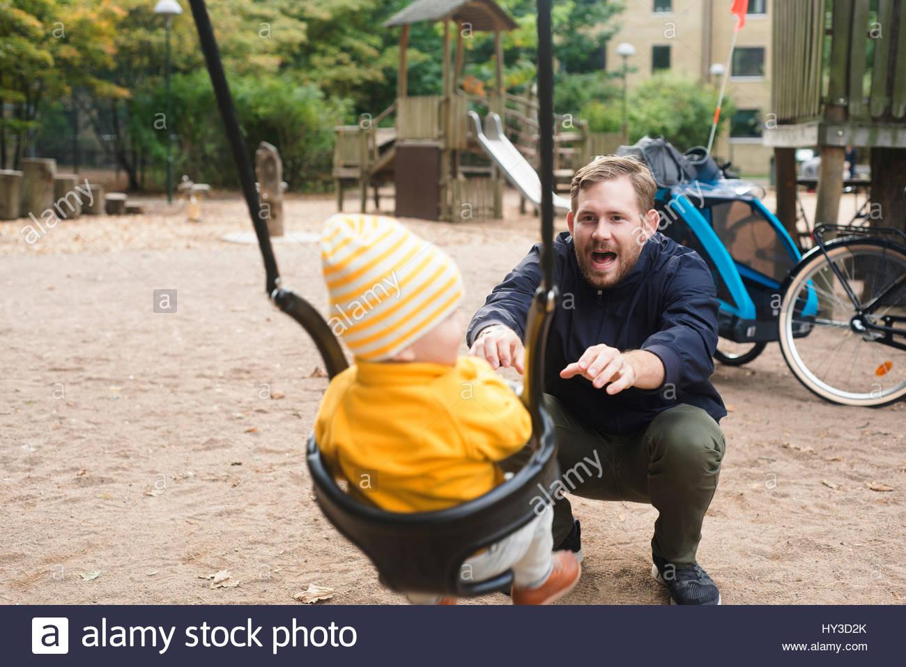 La Svezia, skane, Malmo, padre figlio oscillante ( 12-17 mesi) nel parco giochi Immagini Stock