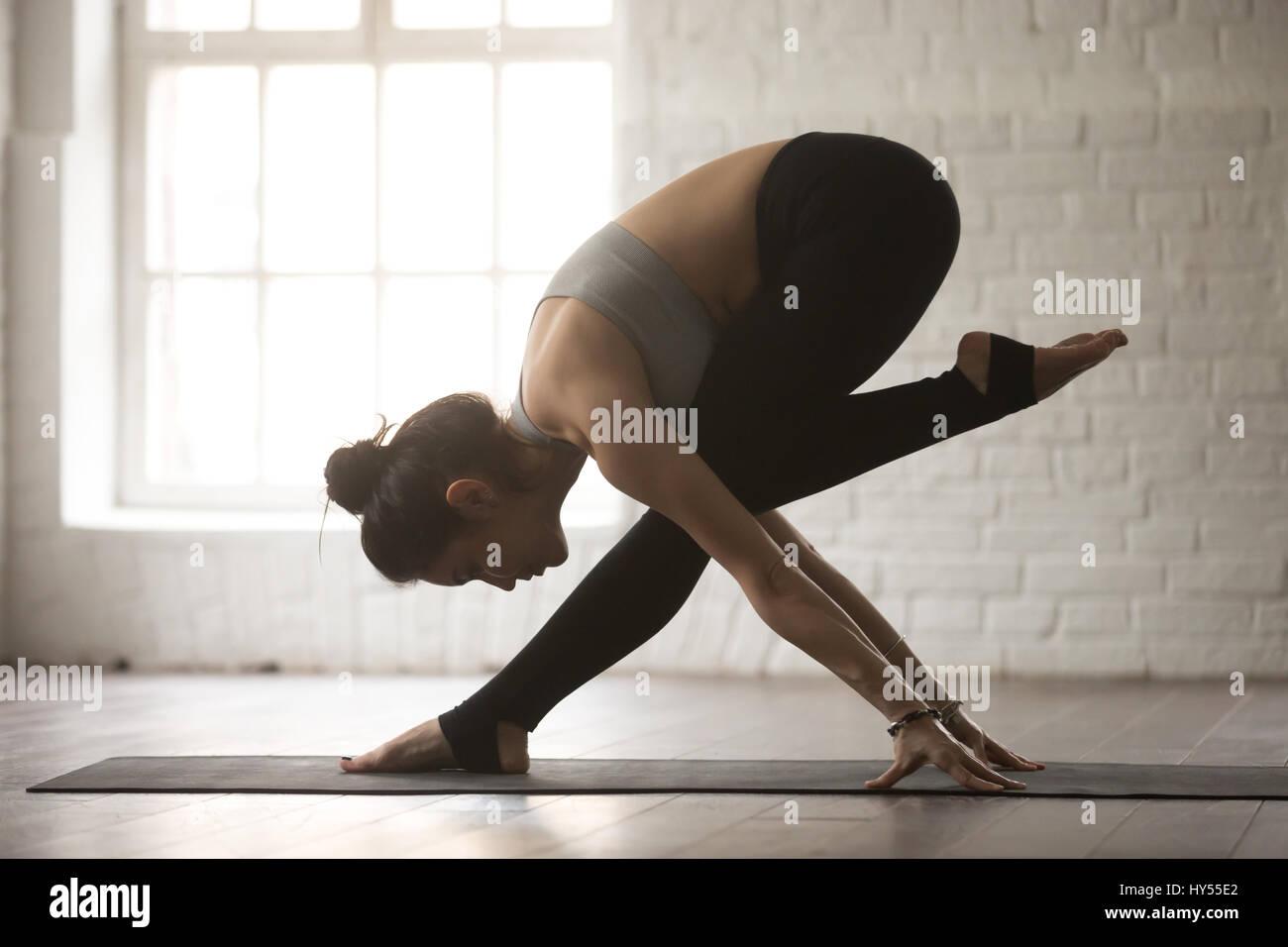 Giovane donna attraente in equilibrio dancing pongono, bianco loft studi Immagini Stock