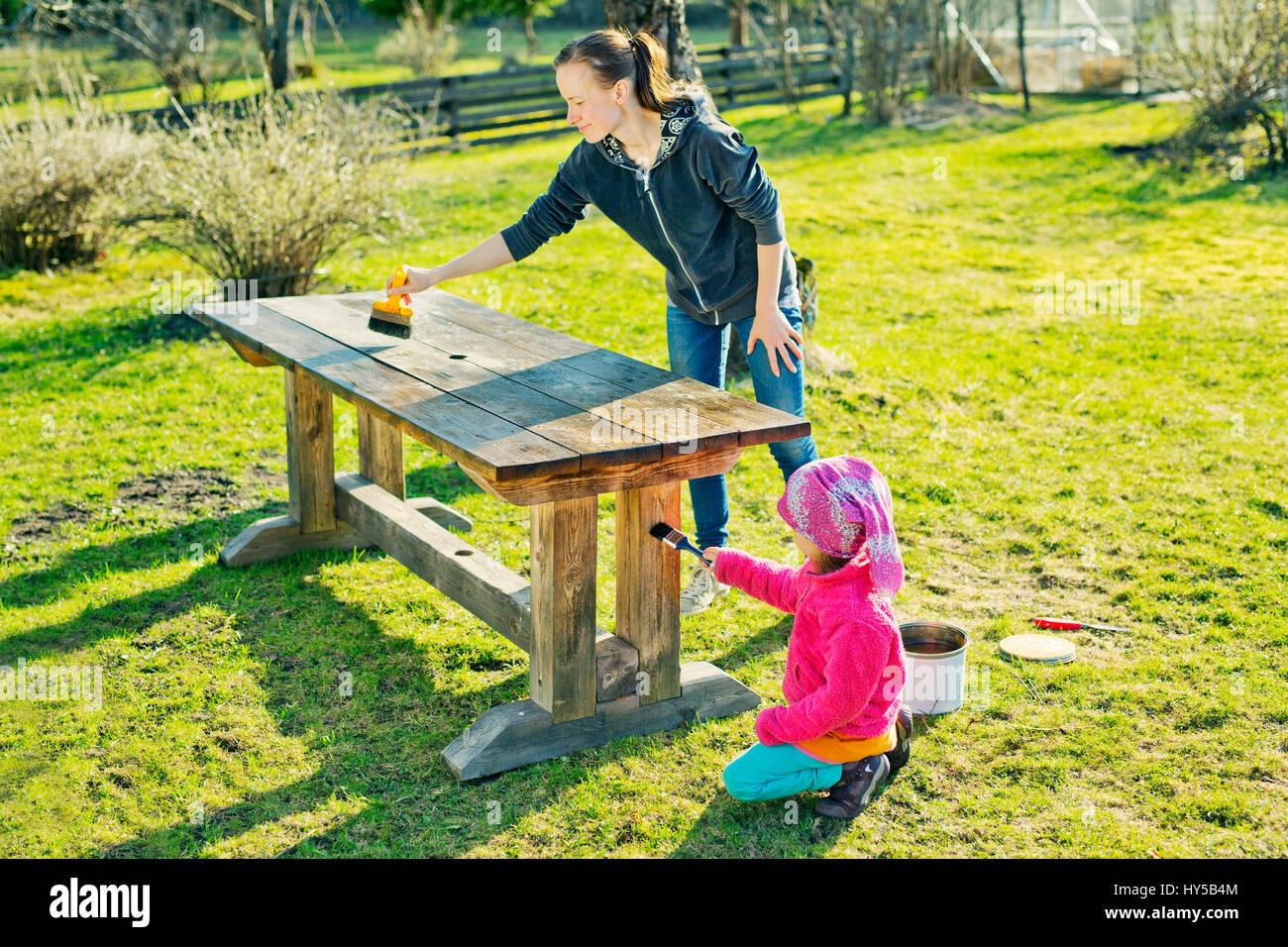 Finlandia, paijat-hame, Heinola, madre e figlia (4-5) lubrificando tavolo di legno in giardino Immagini Stock