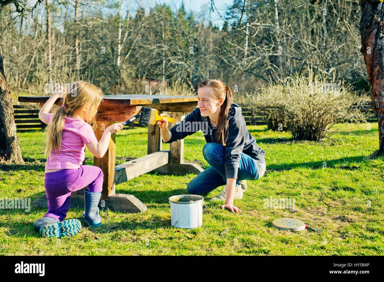 Finlandia, paijat-hame, Heinola, madre e figlia (4-5) pittura tavolo di legno in giardino Immagini Stock