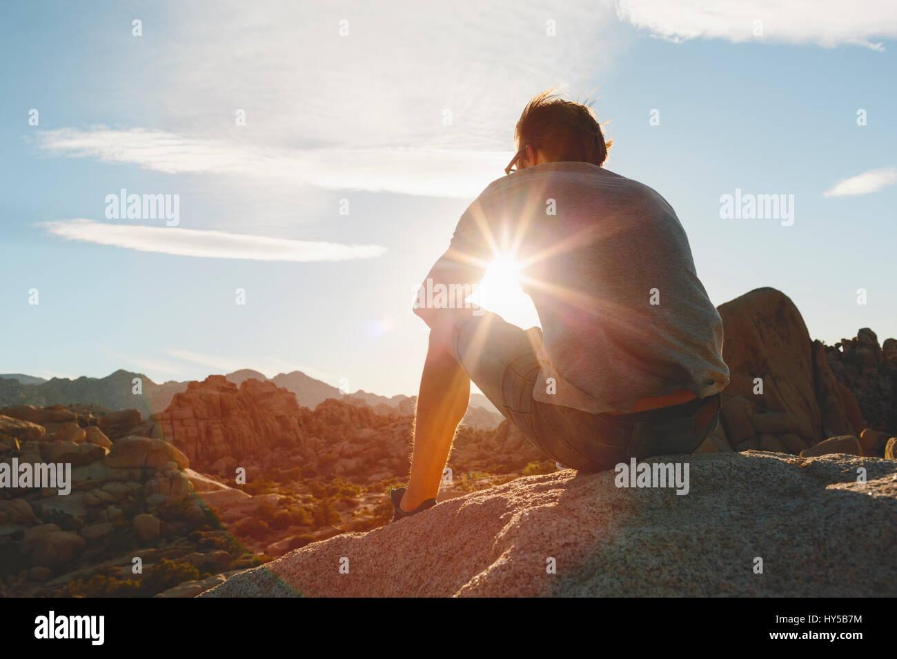 Stati Uniti, California, Joshua Tree National Park, uomo seduto sulla roccia e guardare il tramonto Immagini Stock