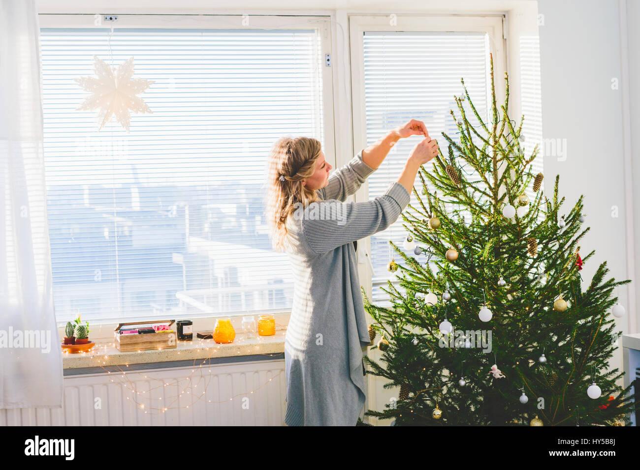 Finlandia, Helsinki, donna decorare albero di natale Immagini Stock