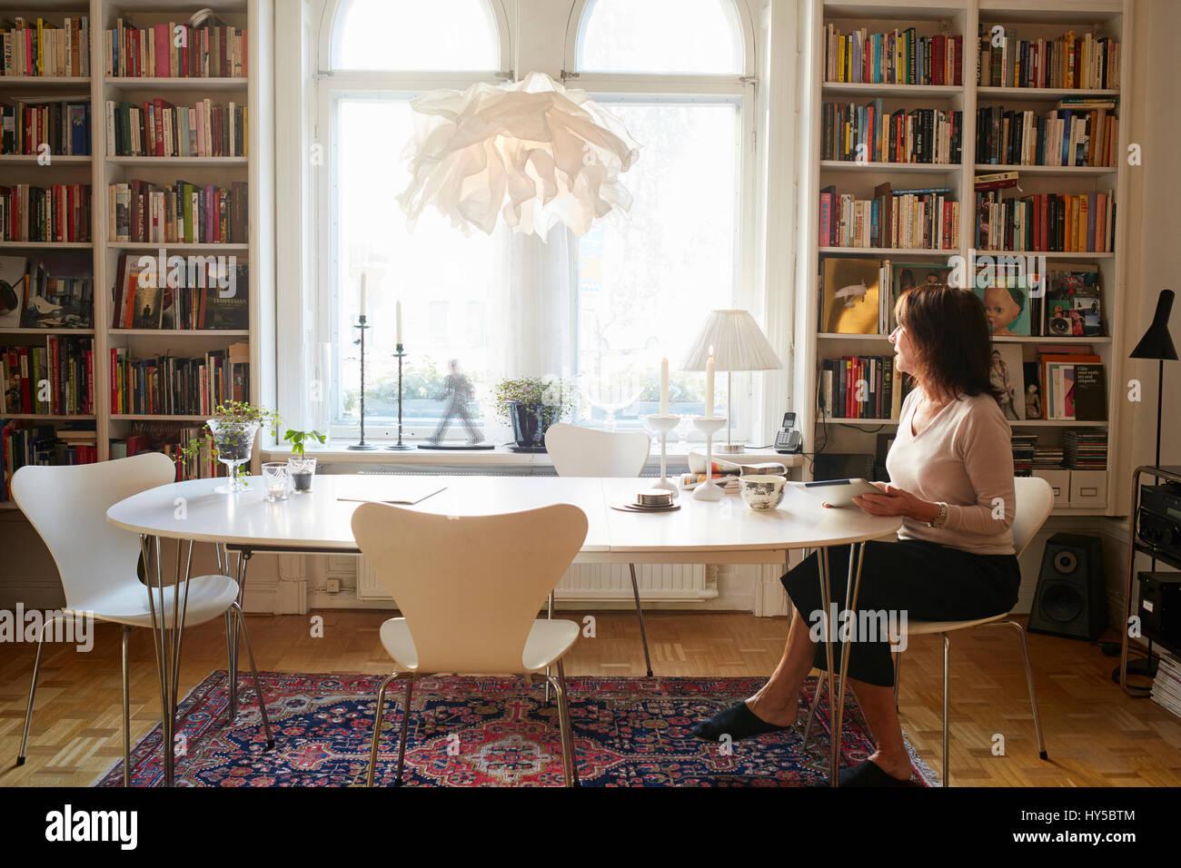 La Svezia, donna seduta da solo al tavolo Immagini Stock