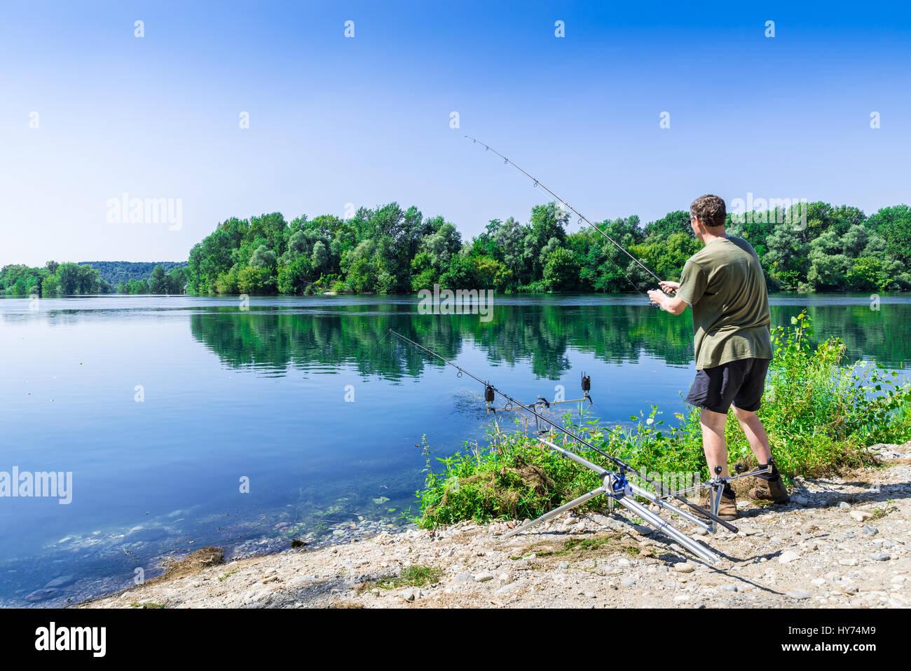Le avventure di pesca, la pesca alla carpa. Il pescatore è la pesca con carpfishing tecnica in acqua dolce, Immagini Stock