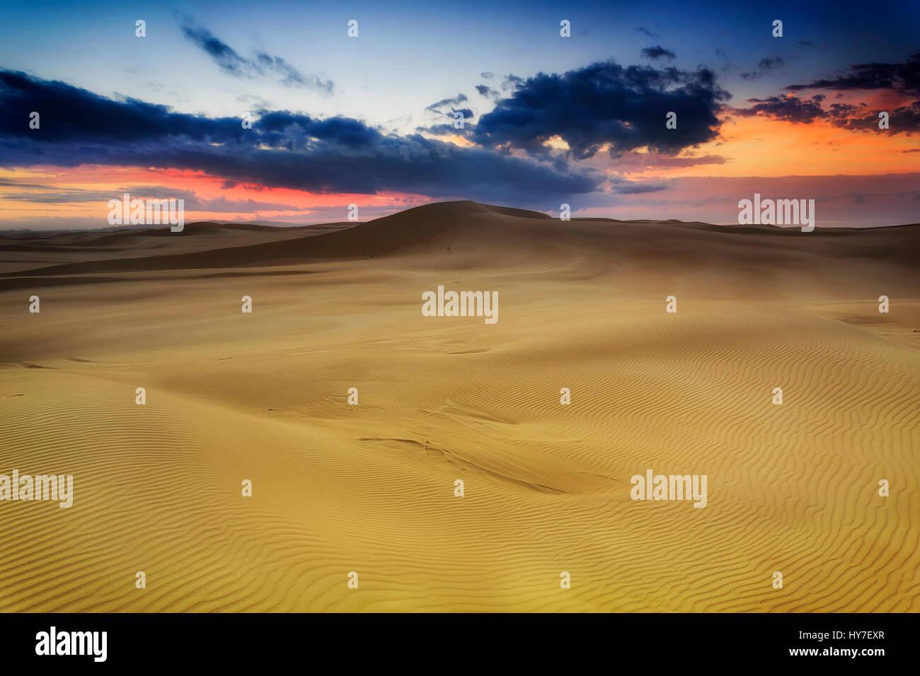 Dune di sabbia dorata di sunrise con gamme di colline di sabbia verso hoziron con red sky vicino Stockon spiaggia Immagini Stock