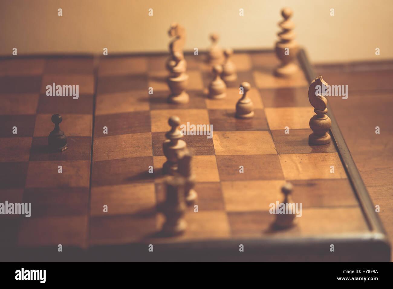 Vecchi pezzi di scacchi su una scacchiera di legno Immagini Stock