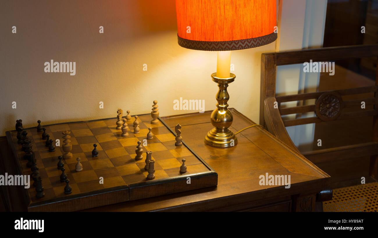 Vecchia scacchiera su scrivania e morbida luce di una lampada da scrivania Immagini Stock