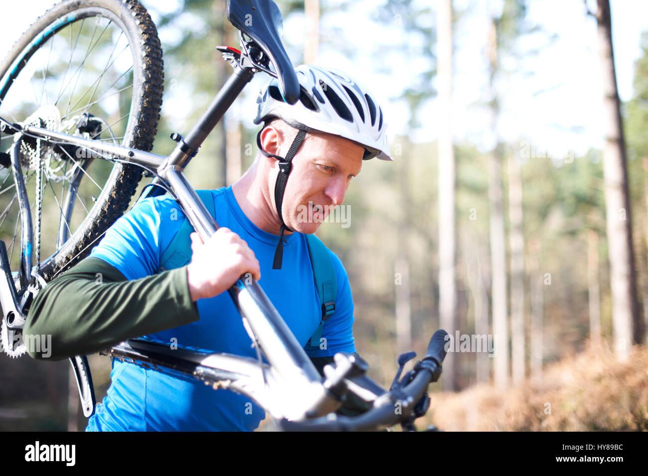 Un uomo porta la sua mountain bike nei boschi Immagini Stock