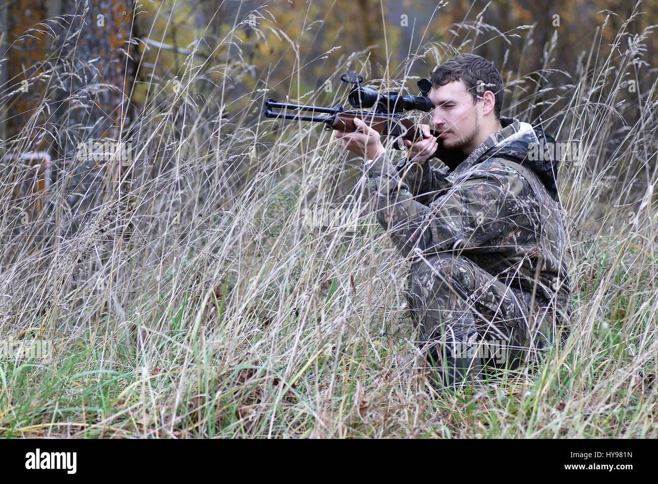 Uomo in mimetica e con armi da fuoco in una foresta la cinghia su una molla hun Immagini Stock