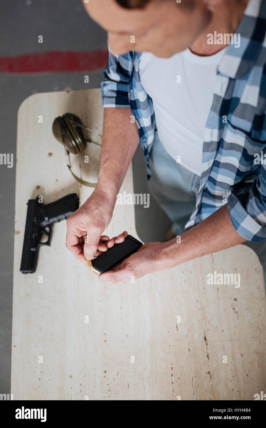 Nice professional marksman ricaricando il fermo della cartuccia Foto Stock