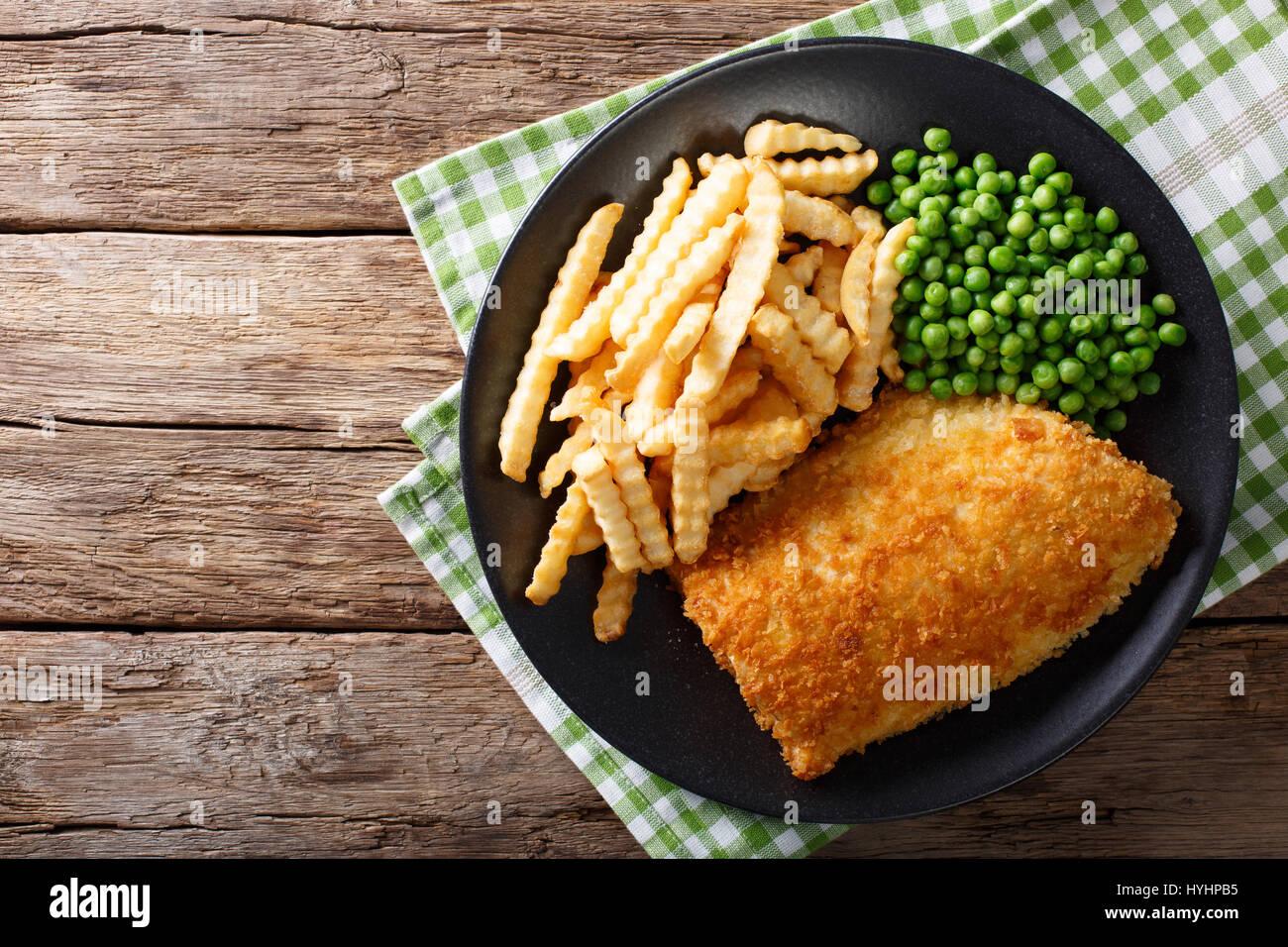 Cibi tradizionali inglesi: pesce e patatine con piselli verdi close-up su una piastra su un tavolo. vista orizzontale Immagini Stock