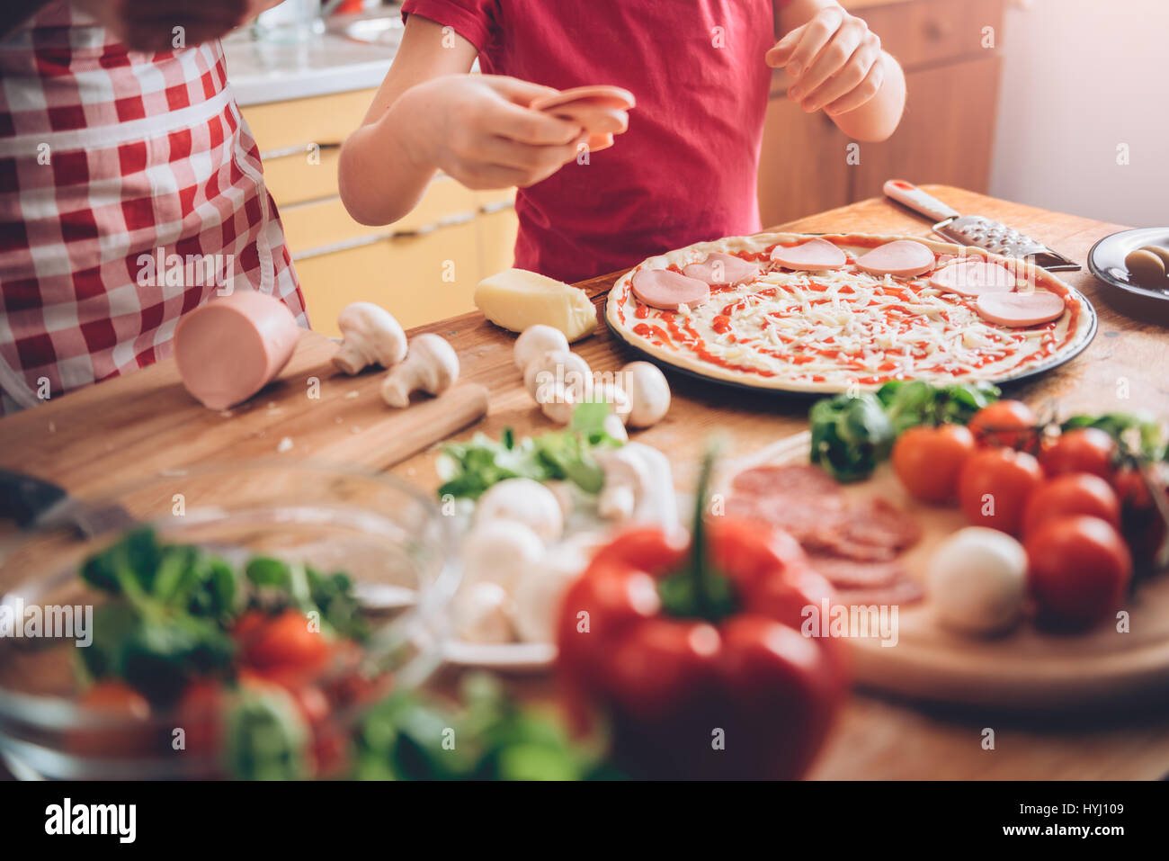 Madre e figlia preparare la pizza in cucina Immagini Stock