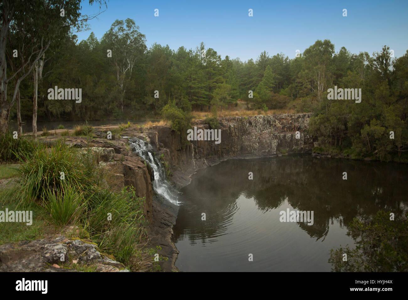 Cascata cascata più alta scogliera rocciosa nelle calme acque della piscina profonda a Tooloom rientra tra Immagini Stock