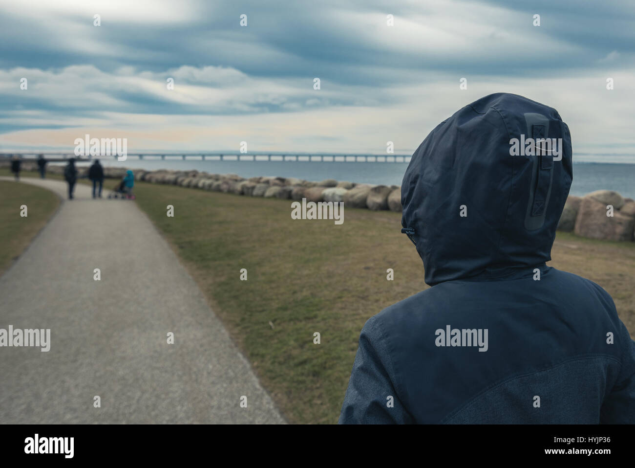 Lonely incappucciati persona femmina da dietro in piedi al mare e guardando a distanza in una fredda giornata invernale, Immagini Stock