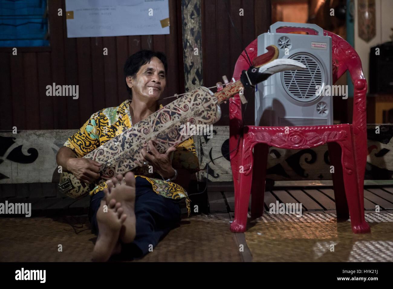 L'uomo gioca sape, tradizionale strumento musicale della comunità dayak, all'interno di Bali Gundi Immagini Stock