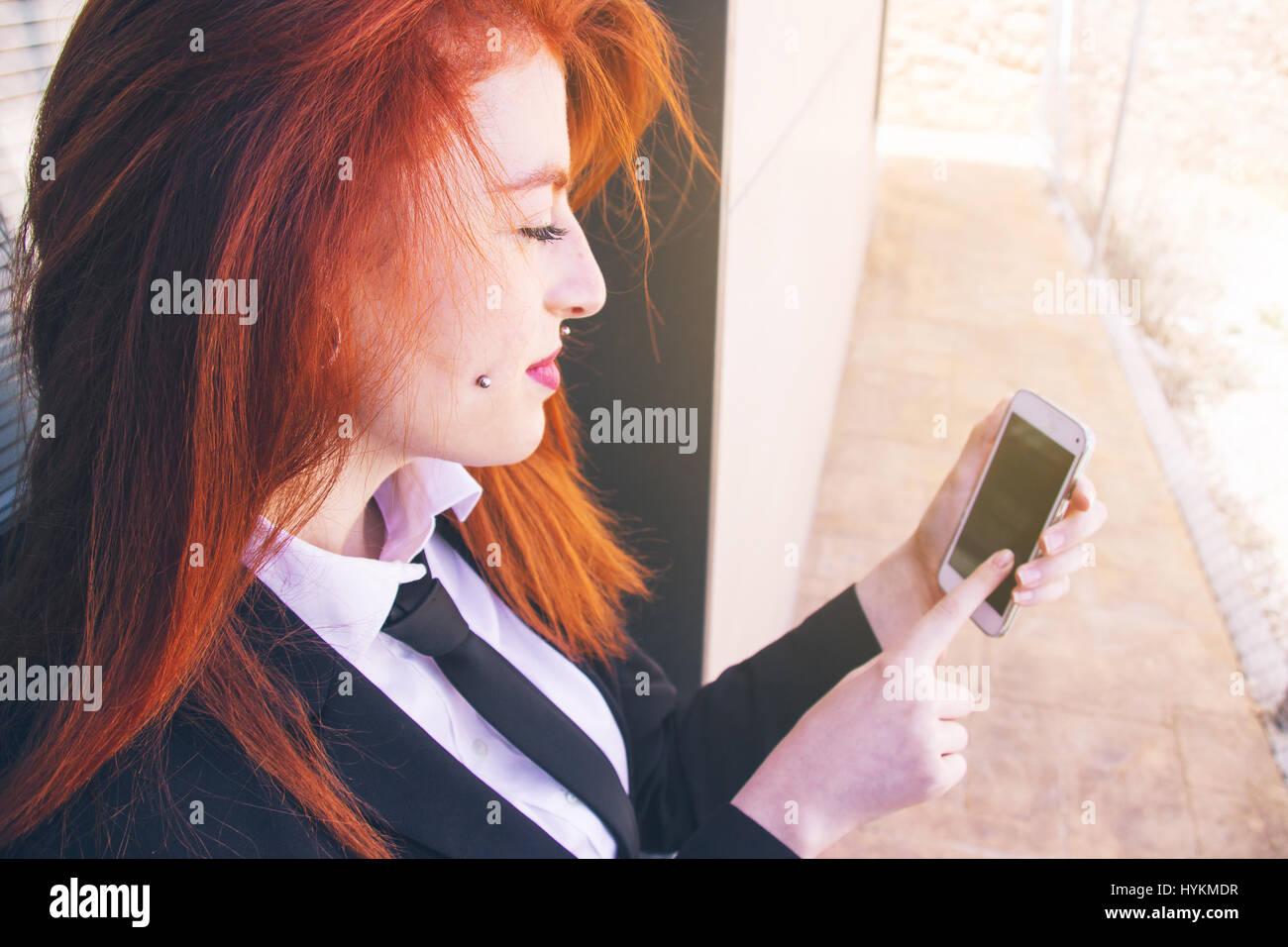 Giovani redhead business donna lavora con il suo smartphone Immagini Stock