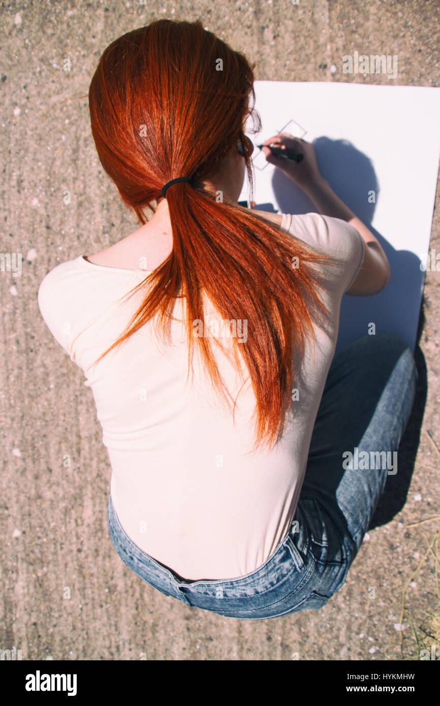 Giovane donna redhead disegnare un poster Immagini Stock