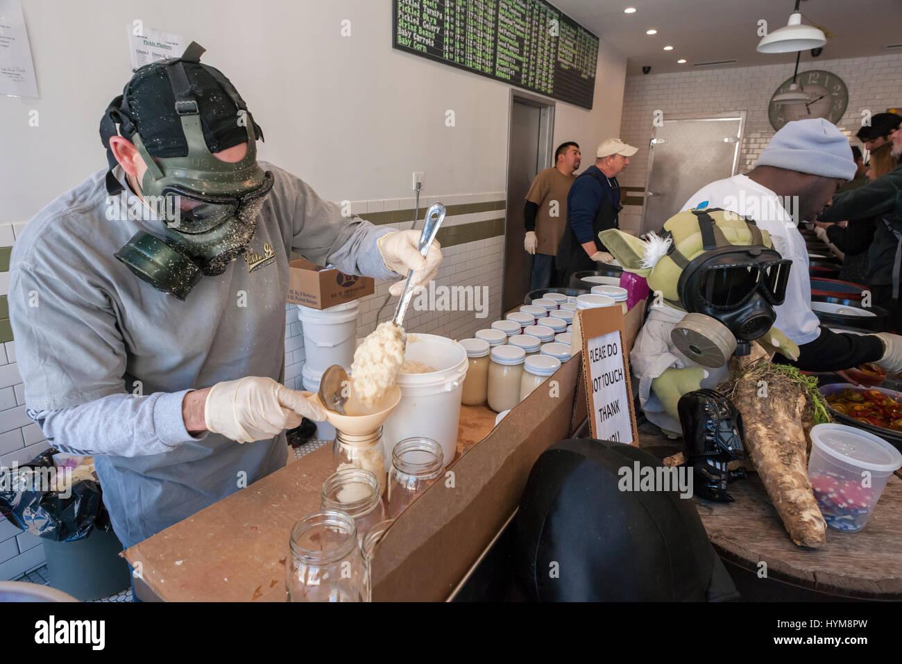 Un lavoratore di indossare un respiratore cucchiai di macinato di fresco il rafano in vasi in corrispondenza della Immagini Stock