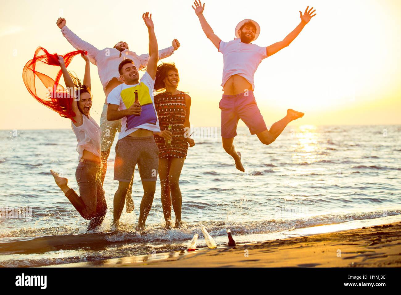 Un gruppo di giovani felici hanno balli sulla spiaggia il bellissimo tramonto estivo Immagini Stock