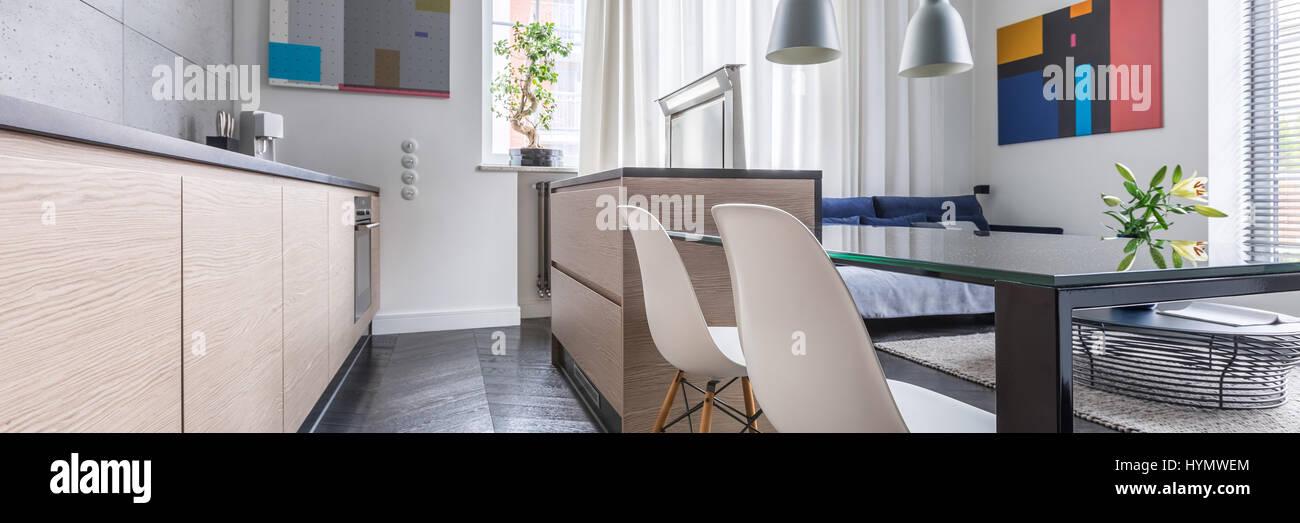 Cucina contemporanea con tavolo e sedie bianche e credenza