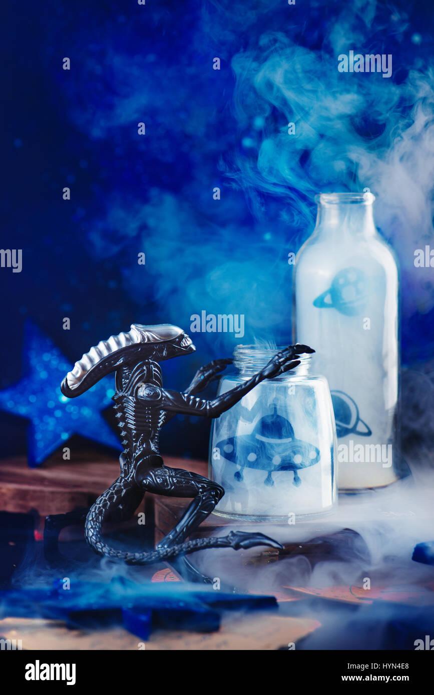 Toy alien con battenti piattini e fumo su sfondo scuro Immagini Stock