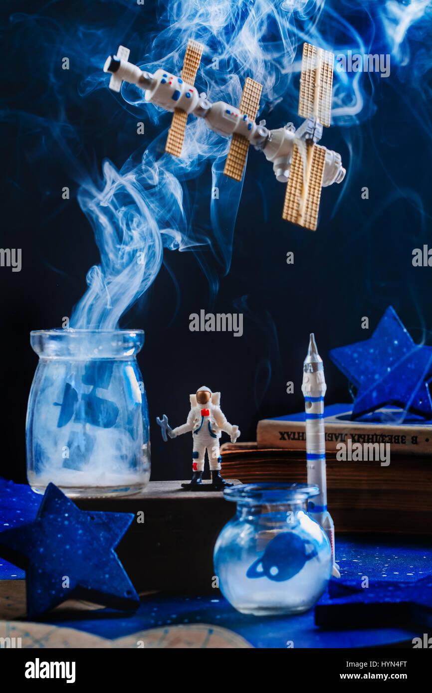 Giocattolo stazione spaziale con l'Astronauta e fumo su sfondo scuro Immagini Stock