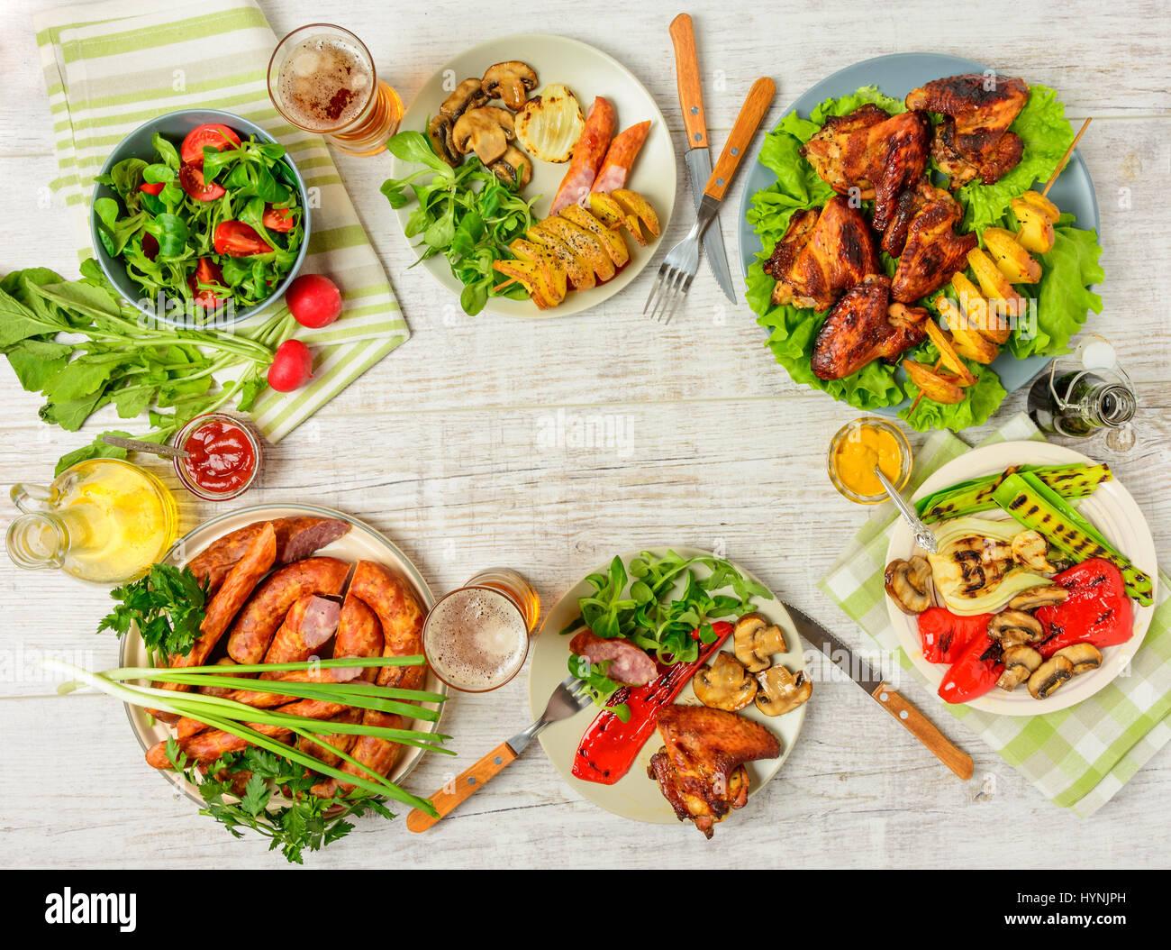 Tavolo per la cena con una varietà di cibo, Alette di pollo fritte, salsicce, verdure grigliate in una padella, Immagini Stock