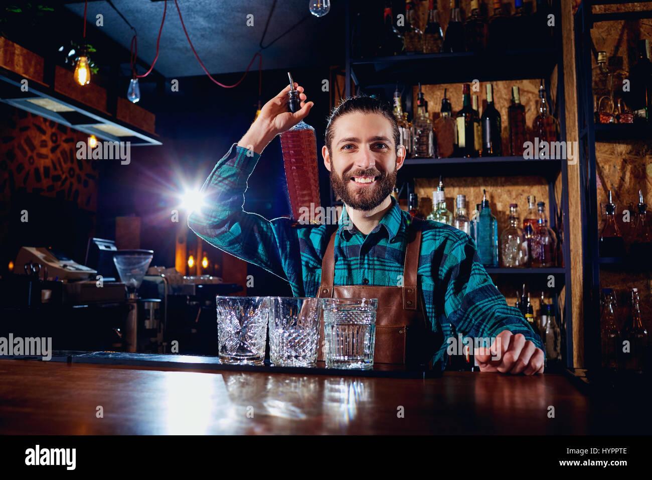 Un barman con bottiglia di alcool sorrisi a ridere al bar Immagini Stock