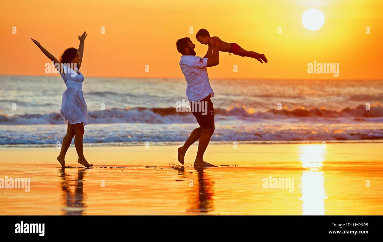 La famiglia felice - padre, madre, figlio bambino a piedi con il divertimento lungo il bordo di mare al tramonto Immagini Stock