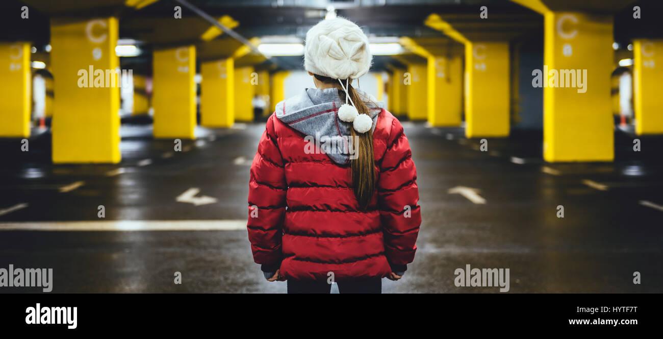 Ragazza che indossa cappello bianco e giacca rossa in piedi in pubblico garage auto Immagini Stock