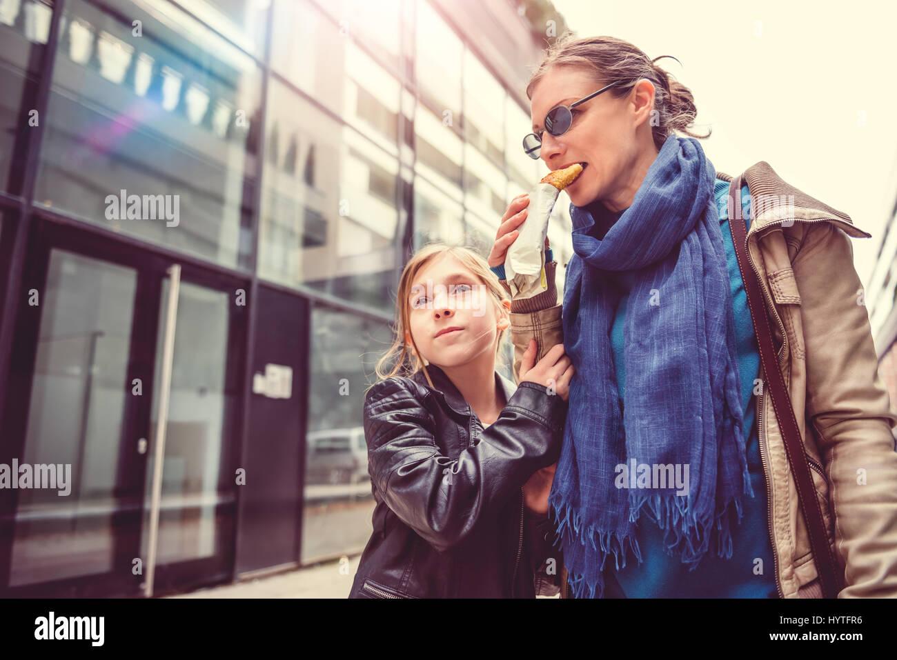 Madre e figlia passeggiando per le strade della città e mangiare panino Immagini Stock