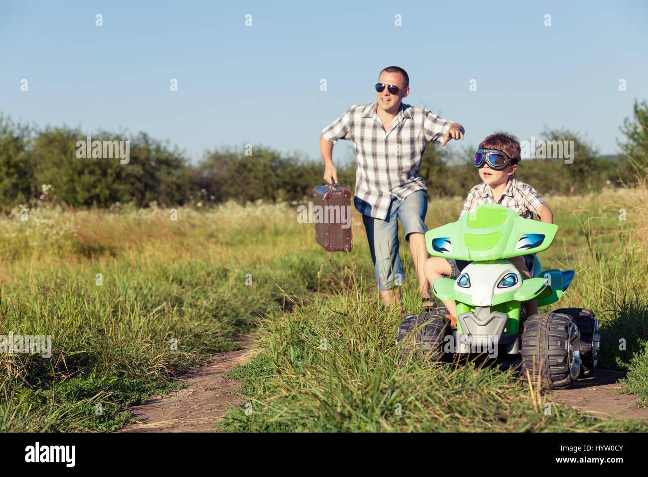 Padre e figlio giocando sulla strada al giorno. Essi guida su quad bike nel parco. Le persone aventi il divertimento Foto Stock