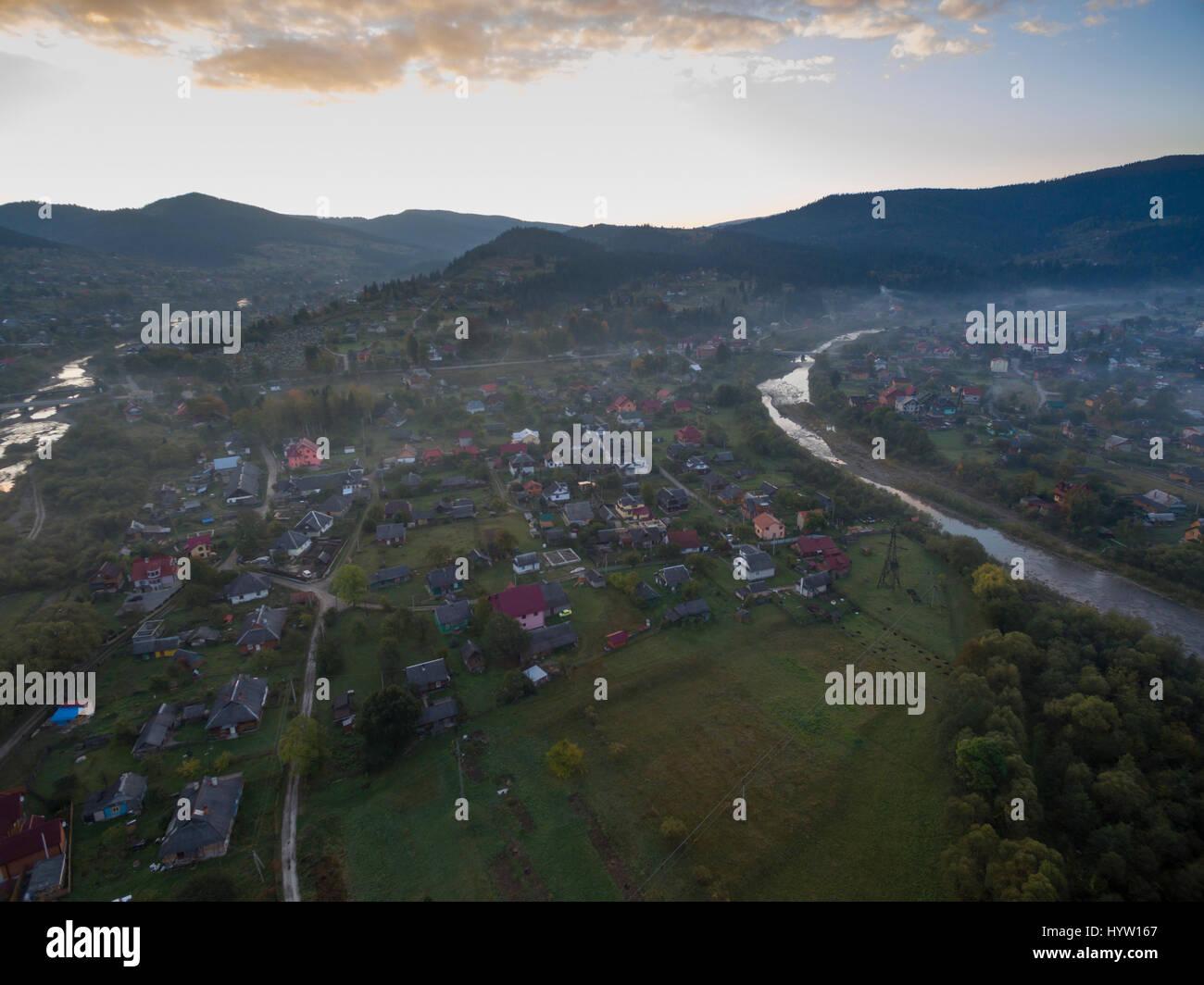 Riprese aeree sopra il villaggio di mykulychyn nella regione dei Carpazi dell'Ucraina occidentale come il sole che Foto Stock