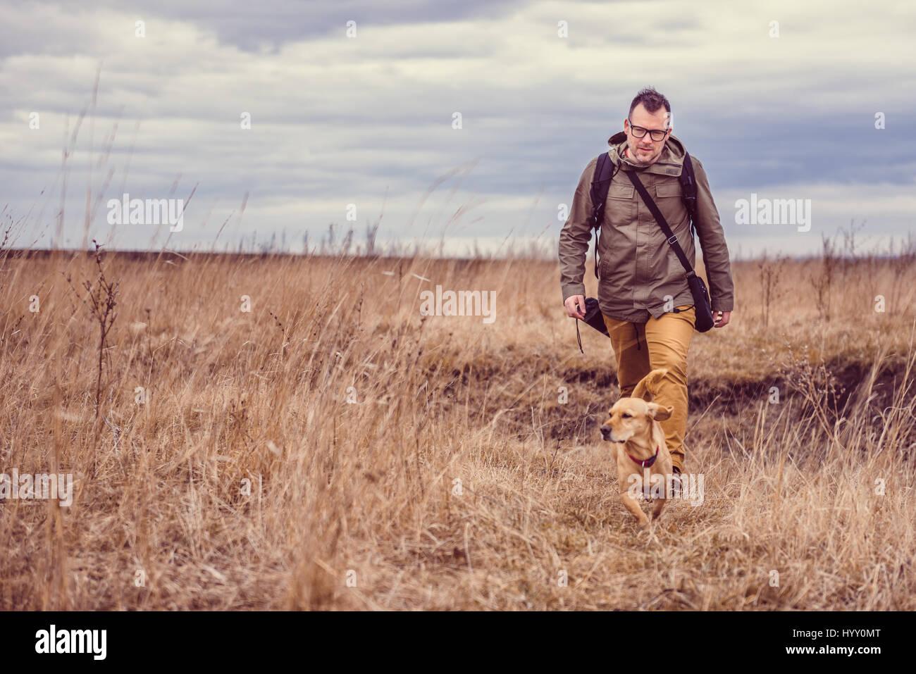 Escursionista e piccolo cane giallo a piedi nella prateria in un giorno nuvoloso Immagini Stock