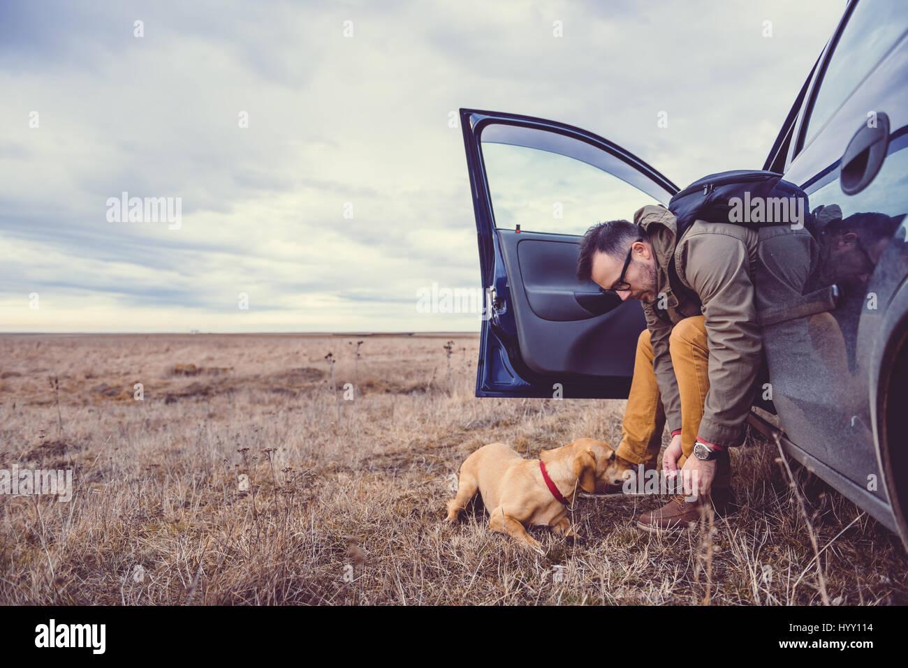 Escursionista seduto in macchina e preparare la loro calzature accanto a lui è un piccolo cane giallo Immagini Stock