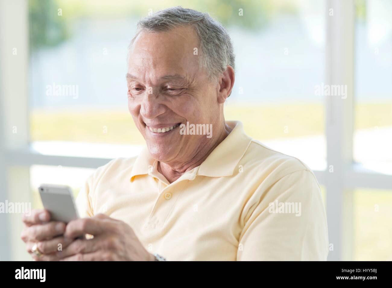 Senior uomo tramite telefono cellulare. Immagini Stock