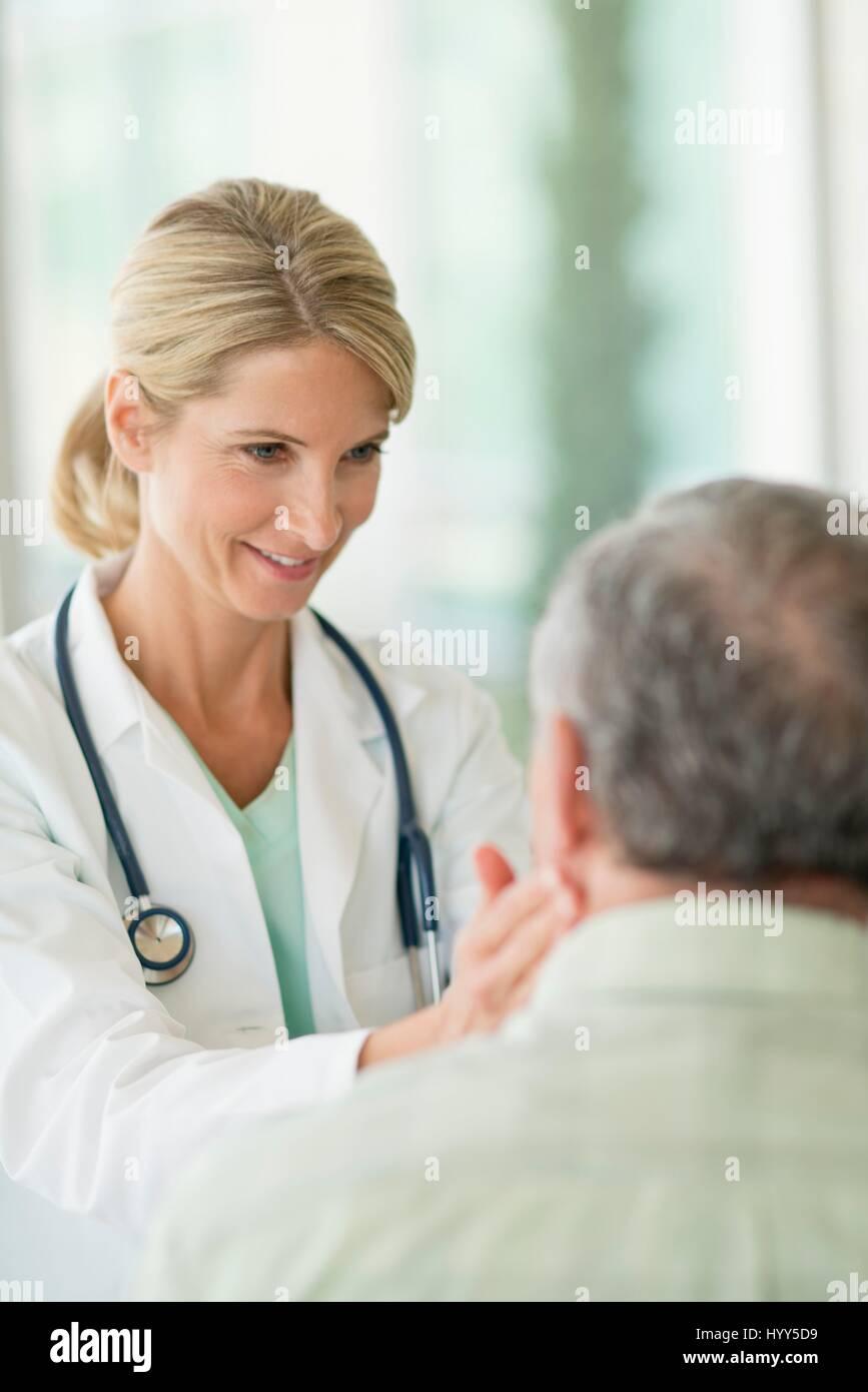 Medico donna toccando uomo senior il collo. Immagini Stock