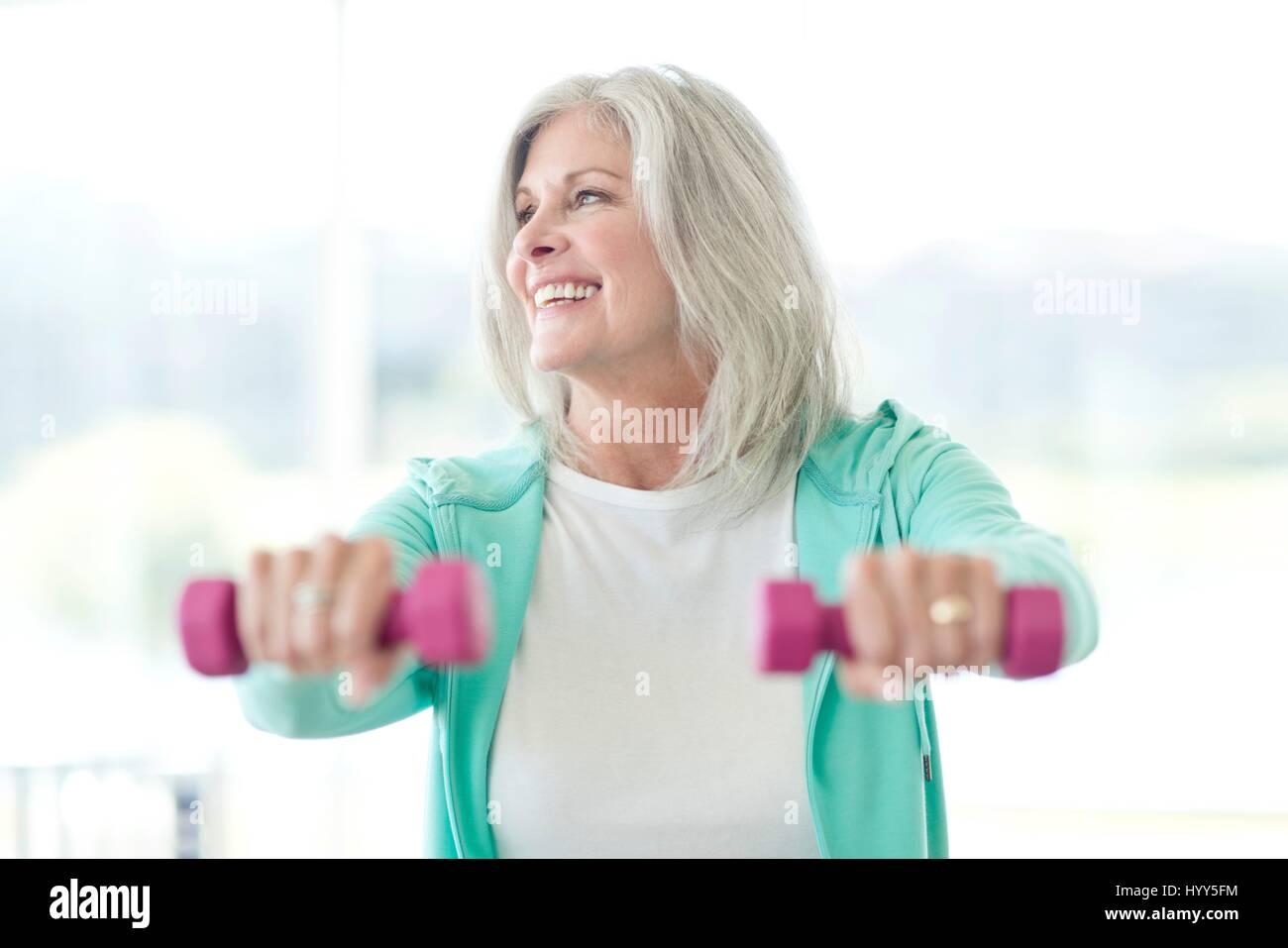 Senior donna utilizzando i pesi a mano. Immagini Stock