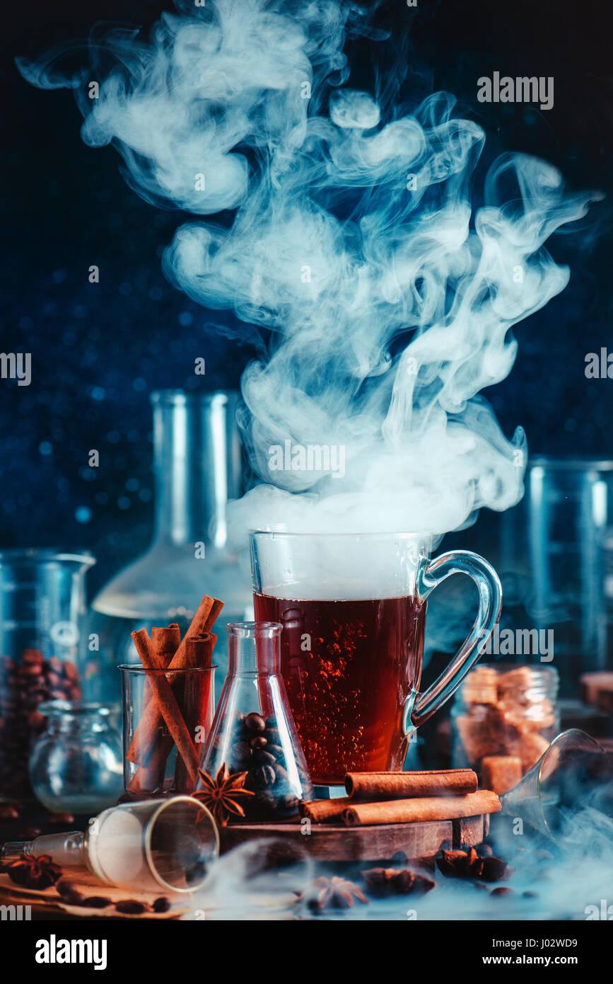 Cibo scuro foto con caffè fumante, spezie, anice e cannella, nel laboratorio di impostazione con imbuto, bicchieri Immagini Stock