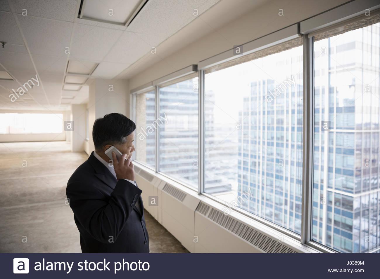 Imprenditore parlando al cellulare in vuote highrise office Immagini Stock