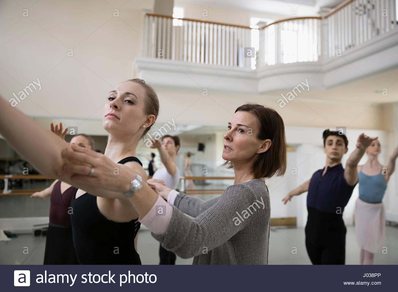 Istruttore bracci di regolazione di femmine della ballerina in studio di danza Immagini Stock
