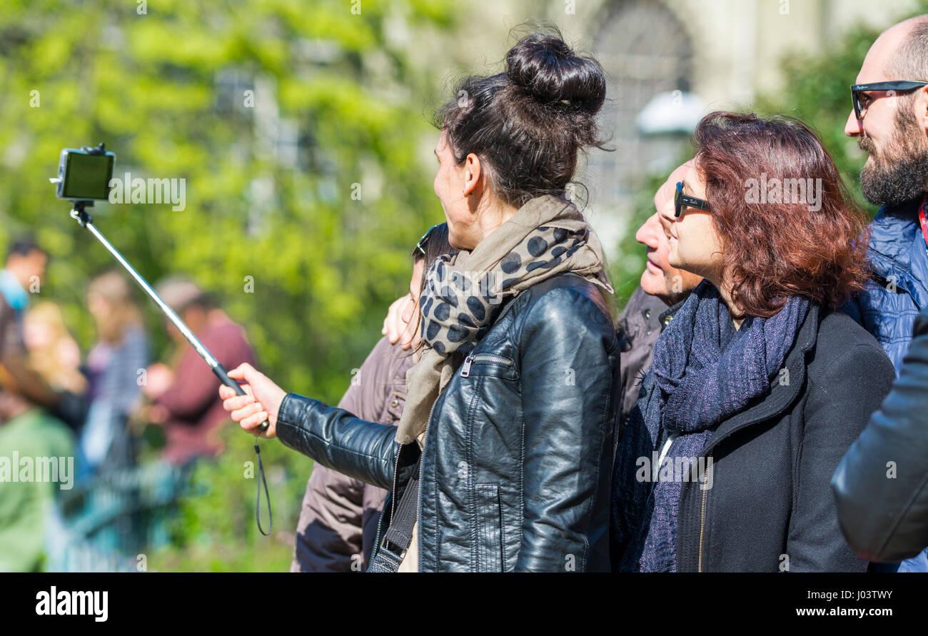 I turisti prendendo fotografie selfis utilizzando uno smartphone attaccato ad un bastone selfie. Immagini Stock